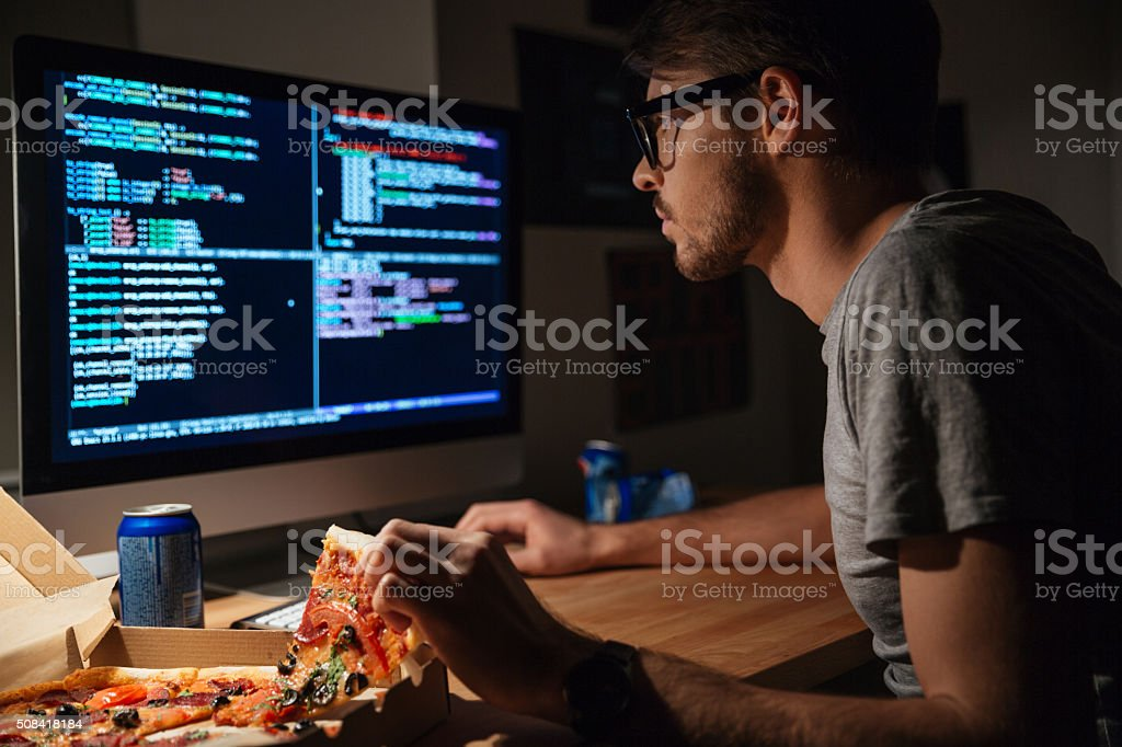 Concentrated software developer eating pizza and coding stock photo