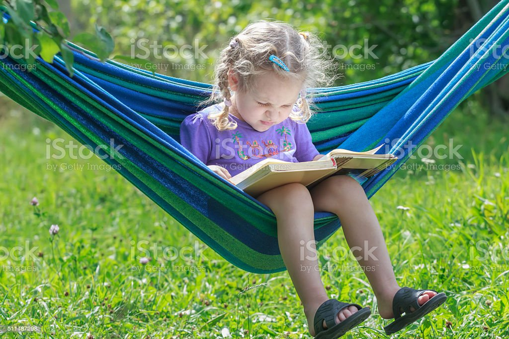 Concentrated two years old girl reading book on hanging hammock stock photo