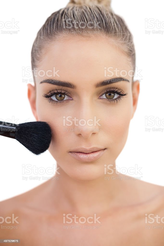 Concentrated woman applying powder on her cheeks stock photo