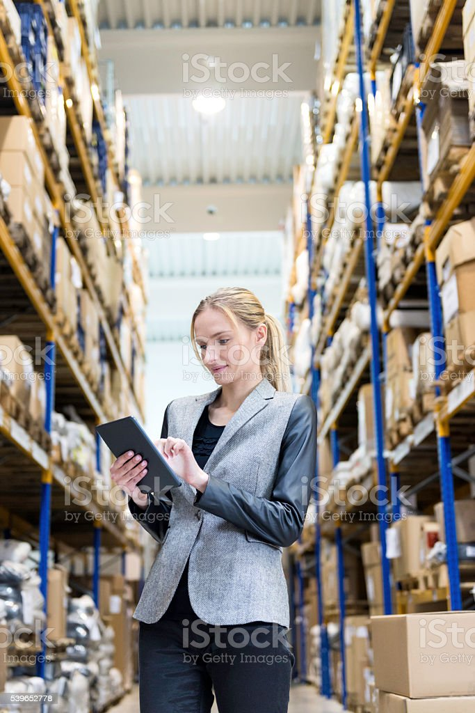 Concentrated woman working with tablet in distribution warehouse stock photo