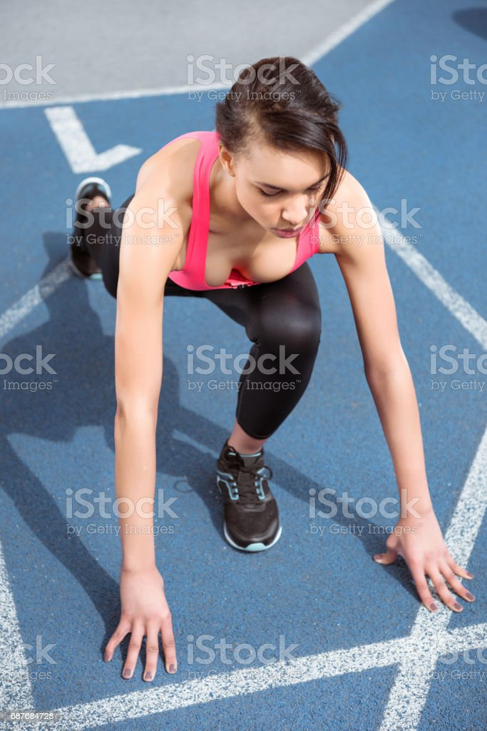Concentrated young fitness woman in sportswear on starting line ready to run stock photo