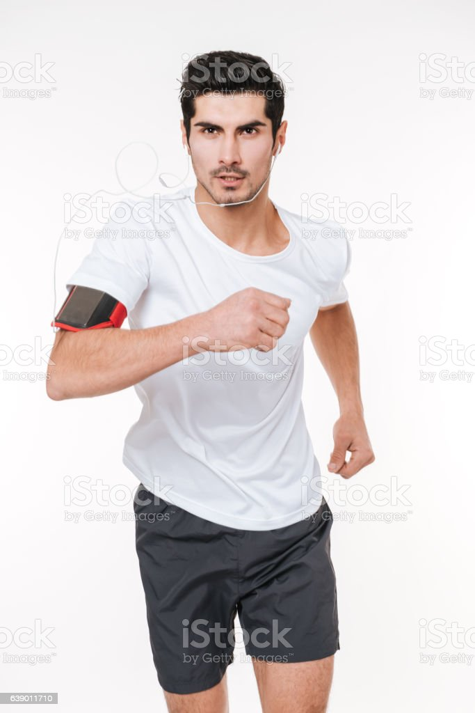 Concentrated young sports man with earphones running stock photo