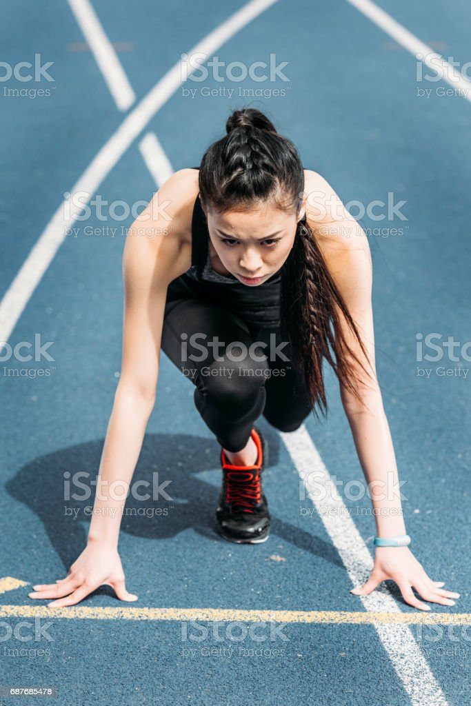 Concentrated young sportswoman in starting position on running track stadium stock photo