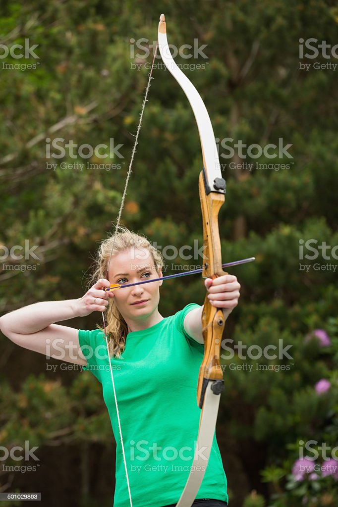 Concentrating blonde woman practicing archery stock photo