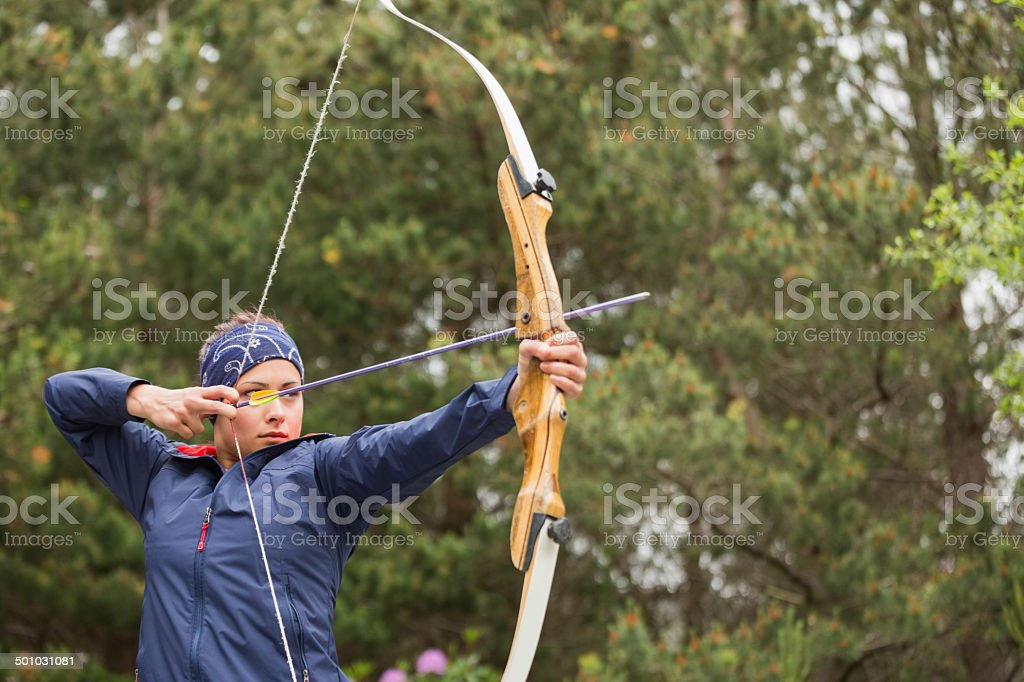 Concentrating brunette practicing archery stock photo