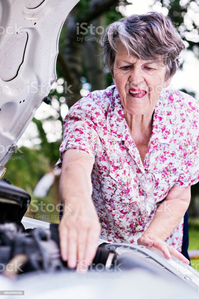 Concentrating hard, old woman tries to fix broken-down car stock photo