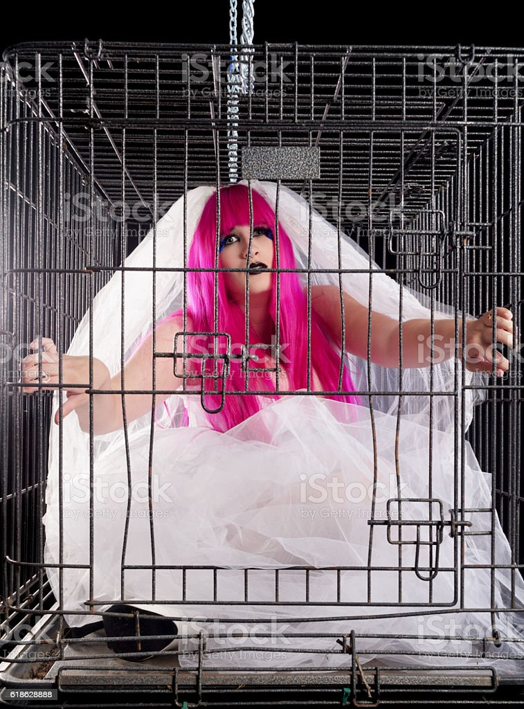 Concept archaic ideas of marriage. Gothic bride in cage. stock photo