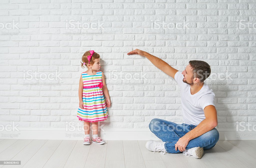 concept. Dad measures growth of her child daughter stock photo