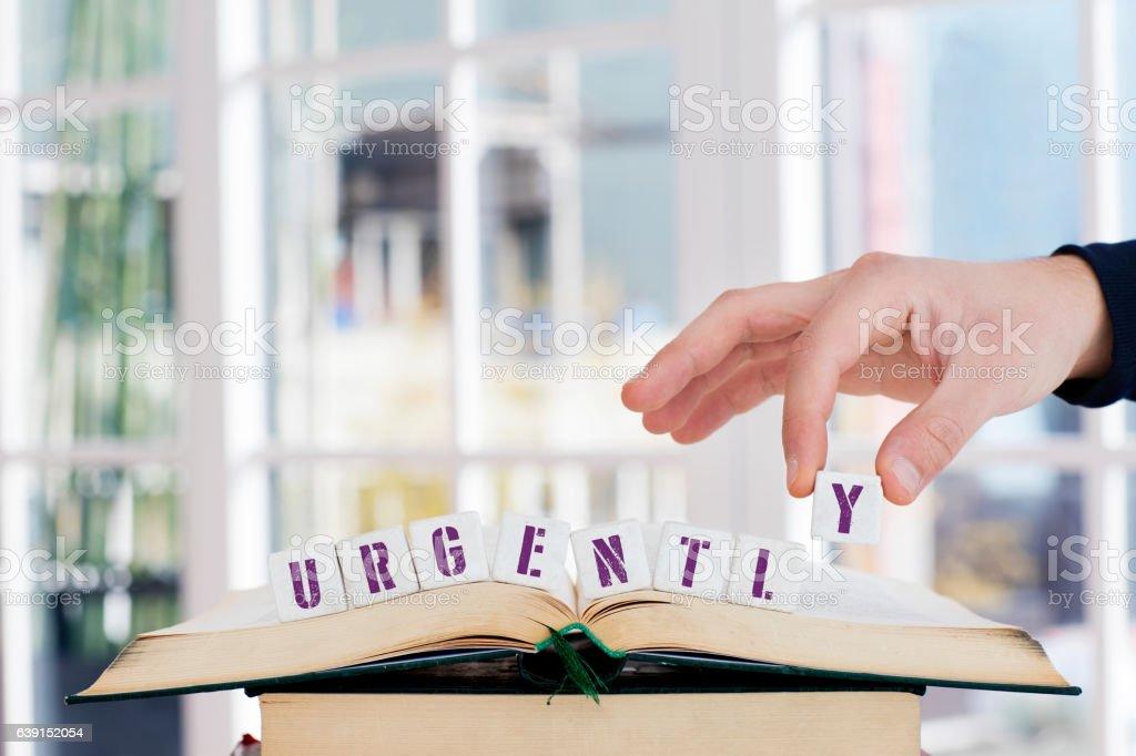 URGENTLY Concept , Hand with alphabet blocks stock photo