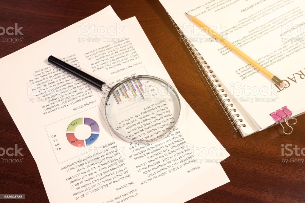 concept of business analytics and statistics, financial statement report, magnifying glass and yellow pencil on office desk stock photo