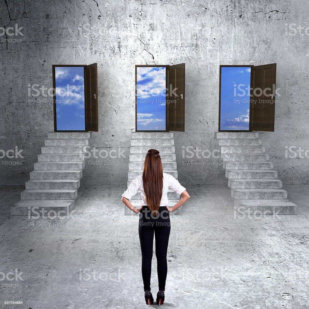 Concept of businesswoman choosing the right door stock photo