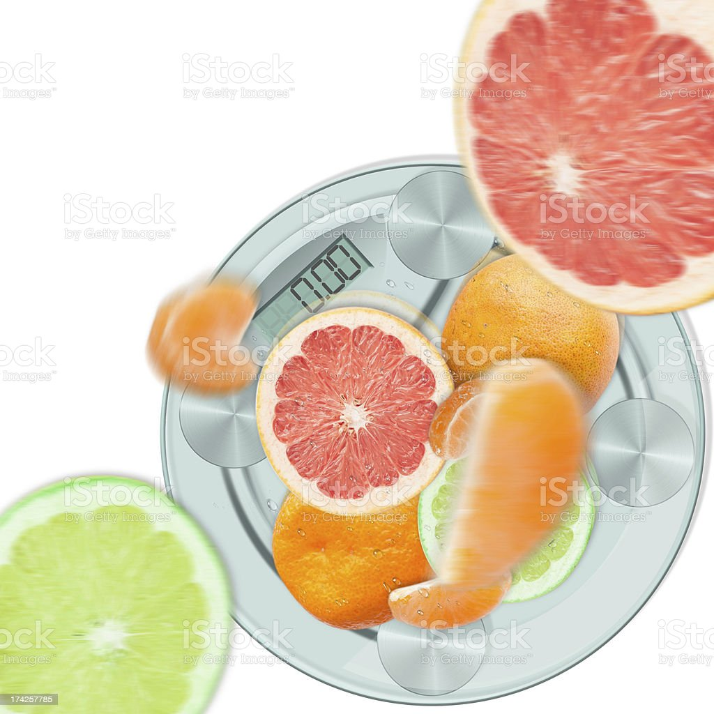Concept of citrus diet. Falling fruit on the scales. royalty-free stock photo