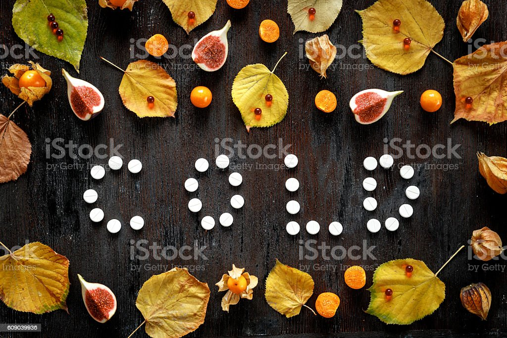 Concept of cold autumn - pills, leaves on dark wood stock photo