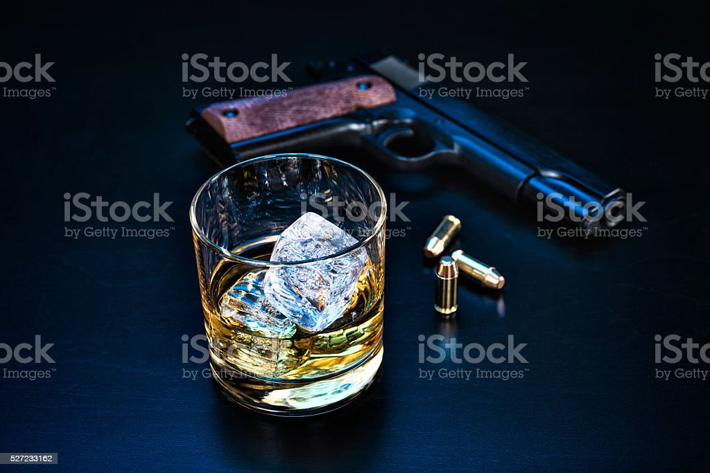 Concept of contemplating suicide with hand gun and alcohol stock photo