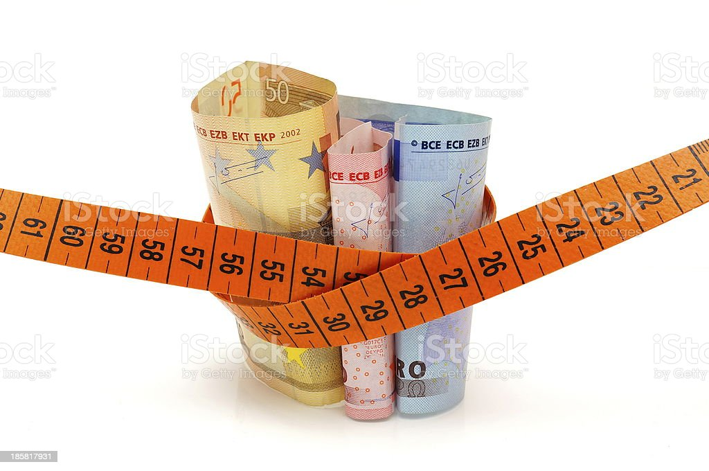 Concept of cutting cost with money and measuring tape stock photo