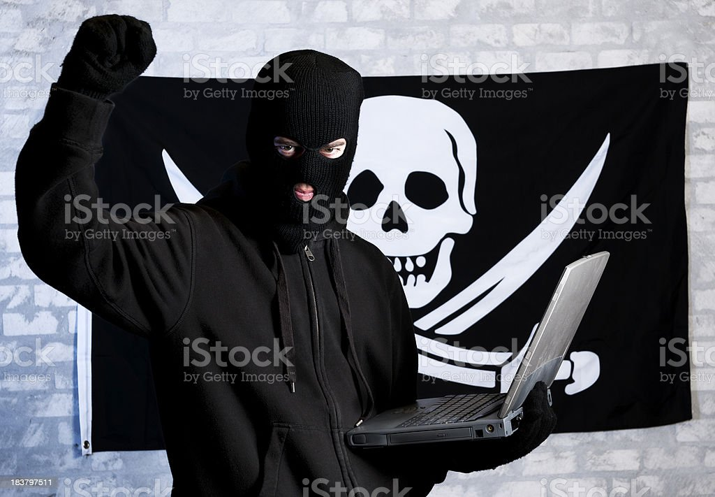 Concept of internet Piracy with a skull and hacker royalty-free stock photo