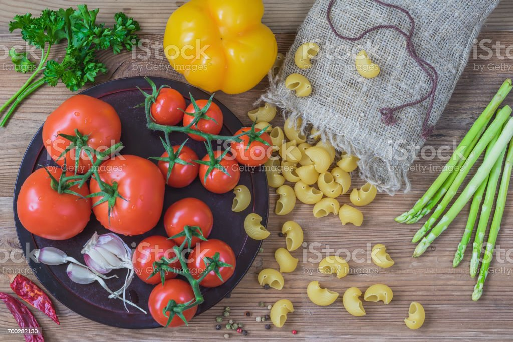 Concept of italian cuisine, vegetarian, healthy food. Ingredients for italian food, dry pasta, vegetables, tomatoes, garlic, asparagus, bell pepper, wooden background stock photo