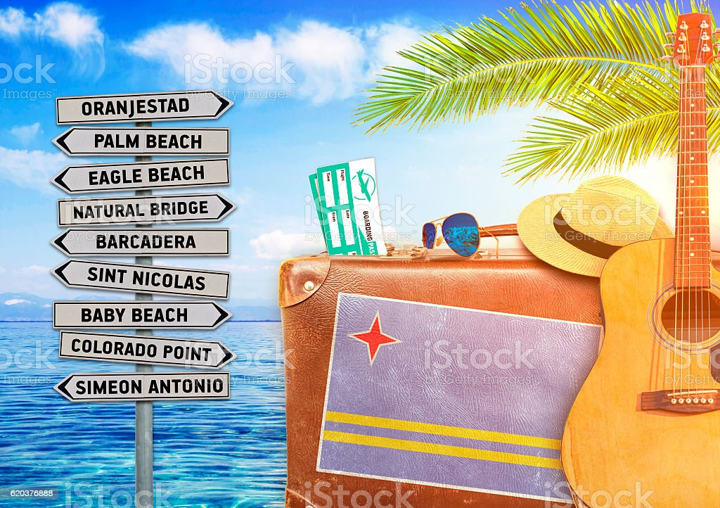 Concept of summer traveling with old suitcase and Aruba town stock photo