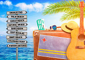 Concept of summer traveling with old suitcase and Aruba town