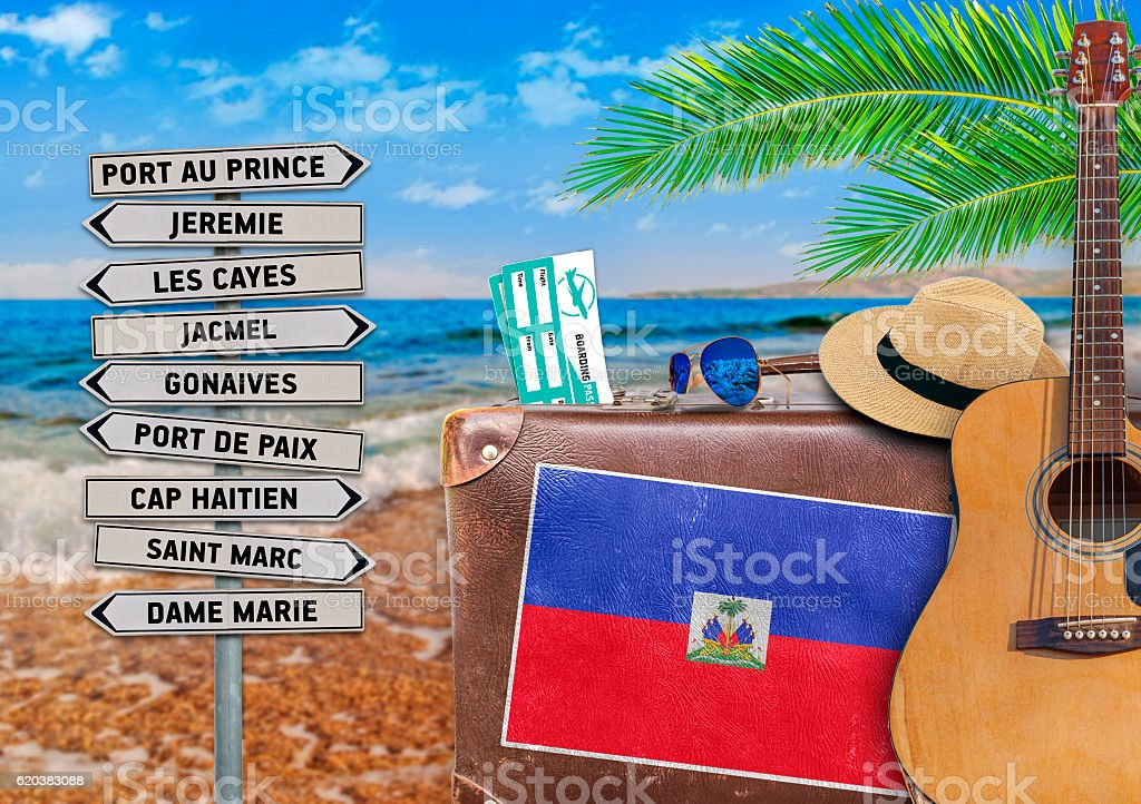 Concept of summer traveling with old suitcase and Haiti town stock photo