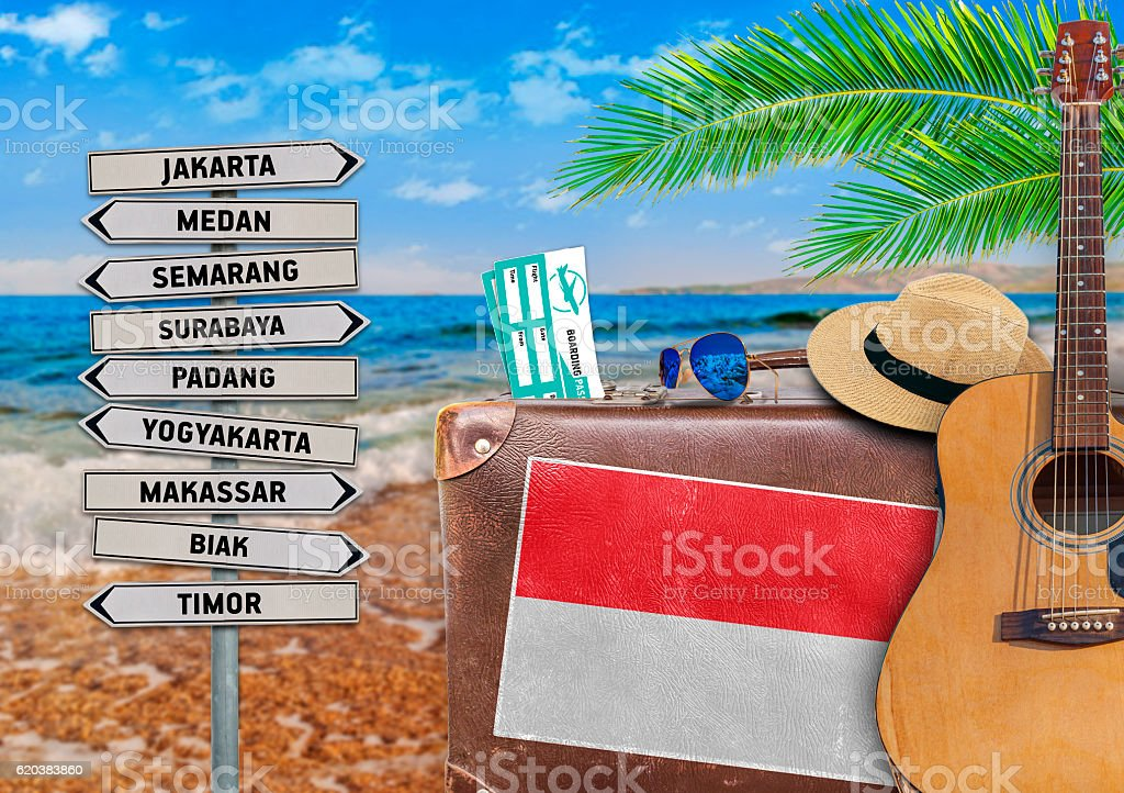 Concept of summer traveling with old suitcase and Indonesia town stock photo