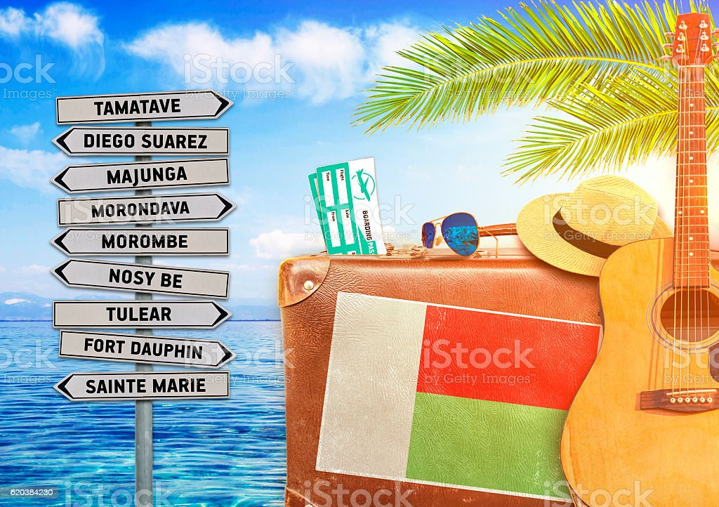 Concept of summer traveling with old suitcase and Madagascar town stock photo