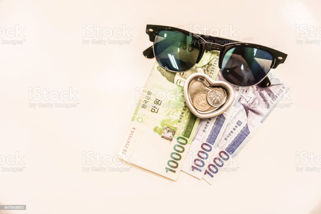 concept of travel in holidays as isolated money in Won currency with sunglasses stock photo