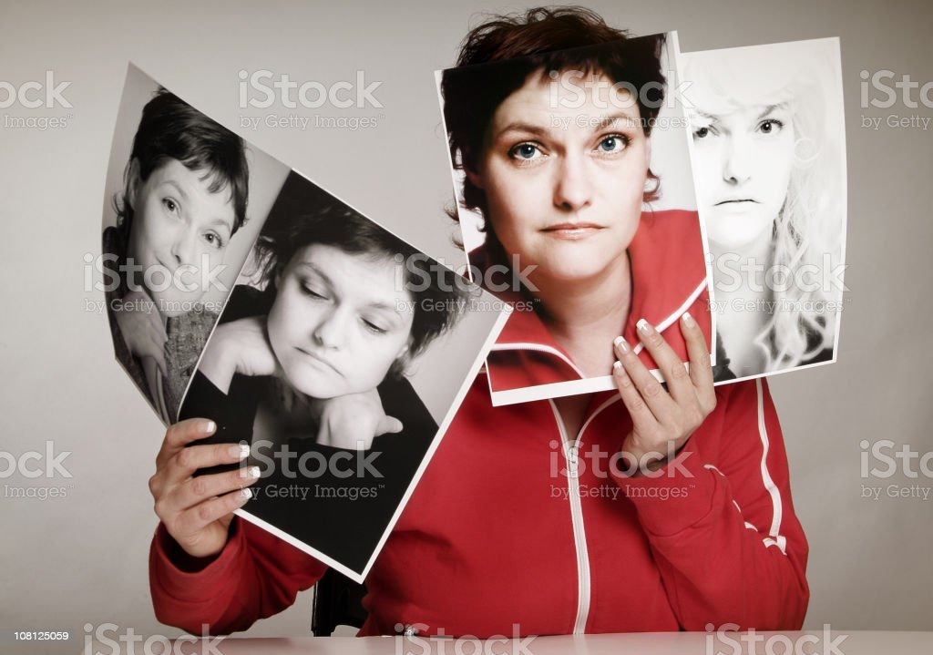 Concept of woman holding pictures of multiple personalities stock photo