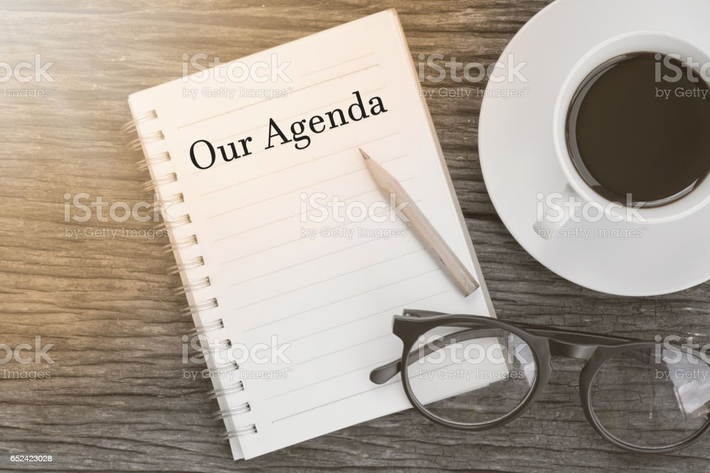 Concept Our Agenda message on notebook with glasses, pencil and coffee cup on wooden table. stock photo