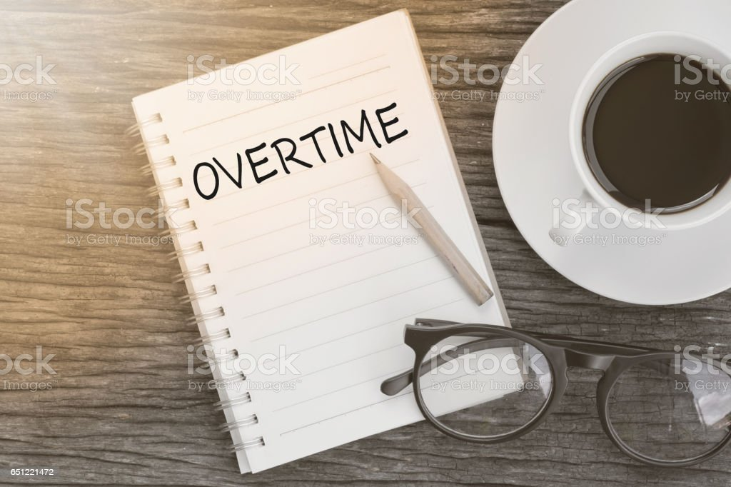 Concept Overtime message on notebook with glasses, pencil and coffee cup on wooden table. stock photo