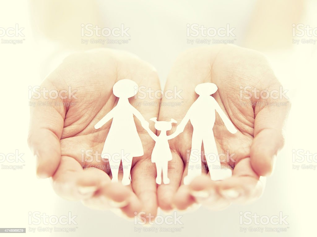 concept. paper figures of family in hands stock photo