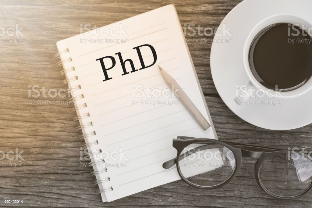 Concept PhD Doctor of  Philosophy Degree Education Graduation message on notebook with glasses, pencil and coffee cup on wooden table. stock photo