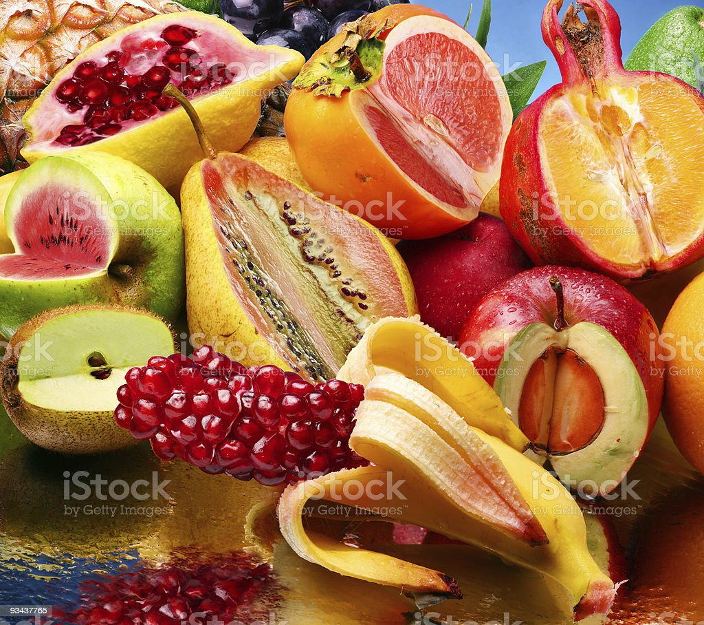 Concept photo of mixed up fruits atop a mirror stock photo
