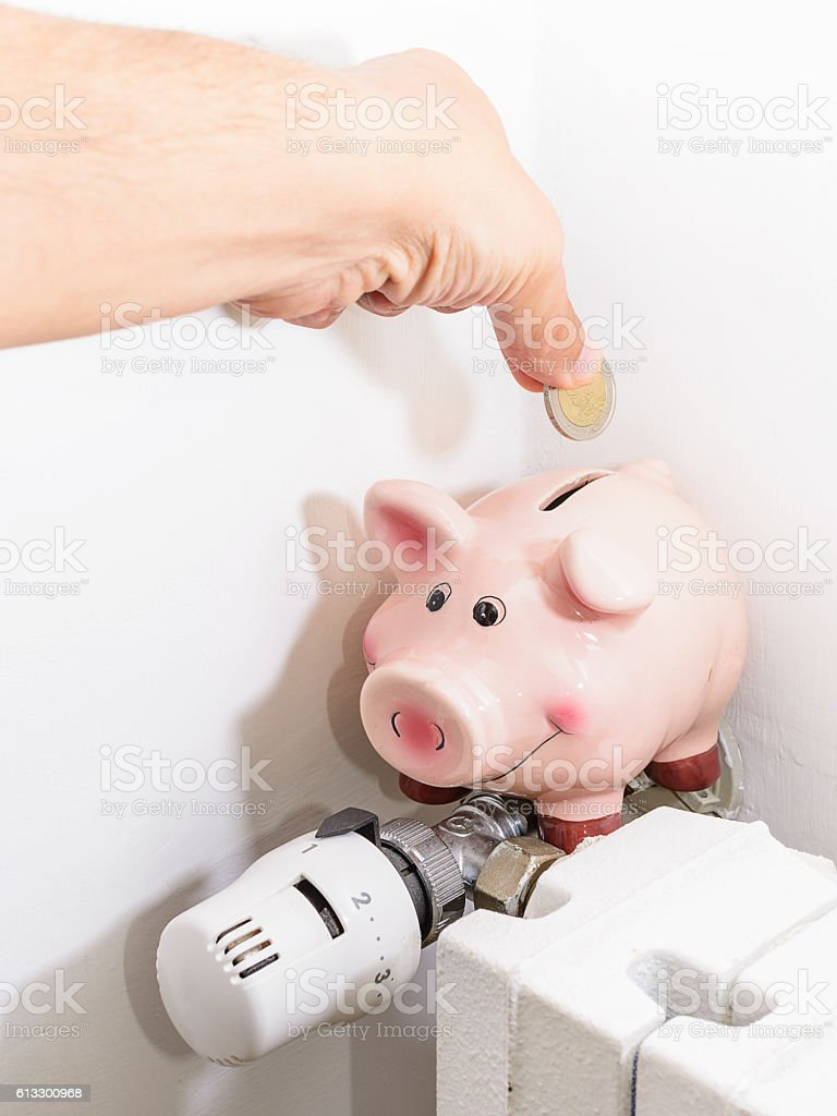 Concept Piggy, the valve on the radiator for saving energy stock photo