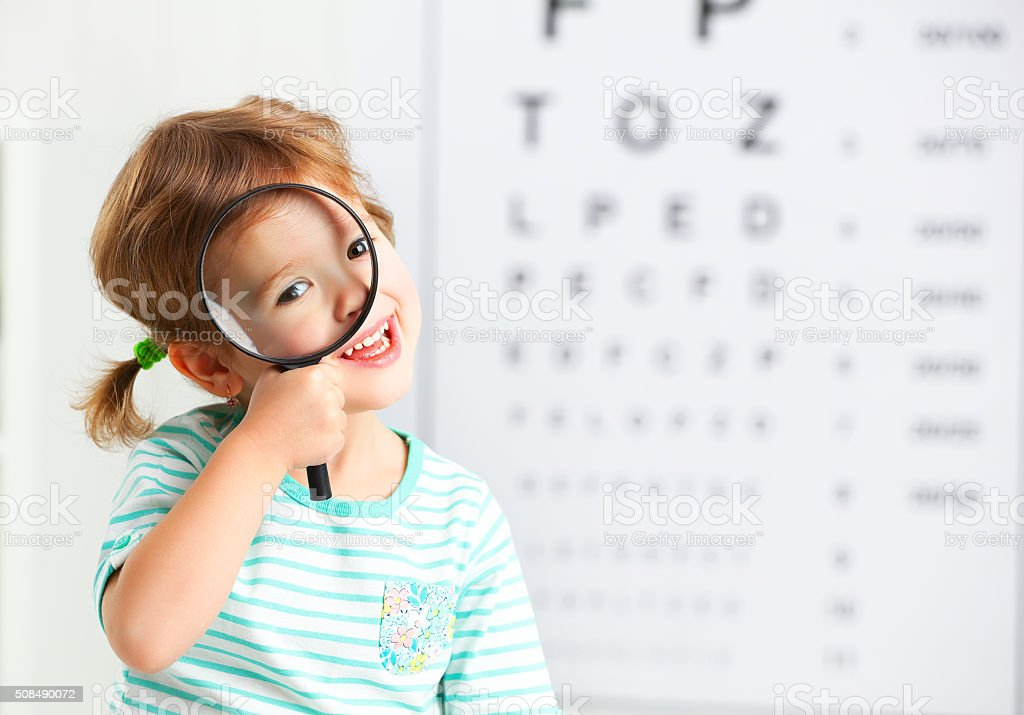 concept vision testing. child girl with a magnifying glass stock photo