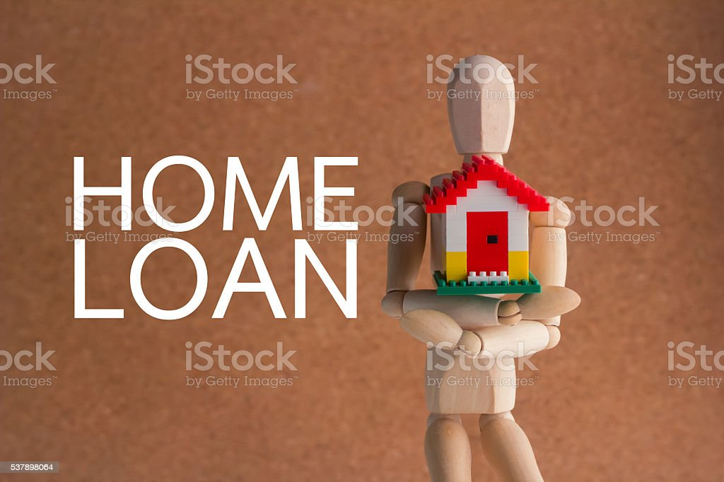 HOME LOAN concept with wooden man hold house plastic model stock photo