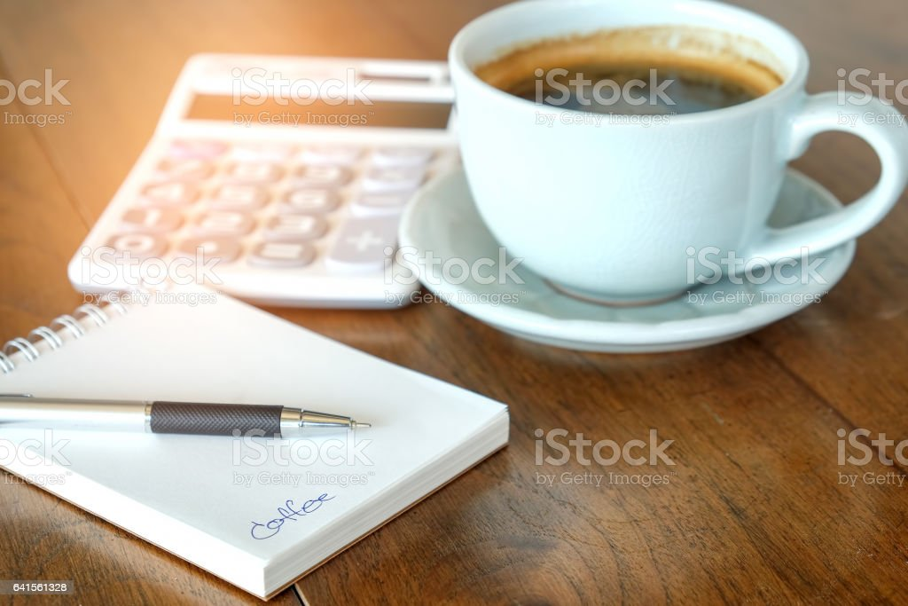 Concept,Coffee cup and notebook with calculator on wooden. stock photo