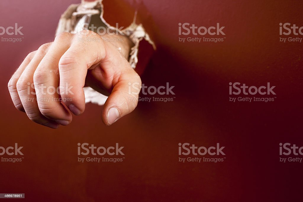 Concepts: Man's hand reaching through a wall to other side. stock photo