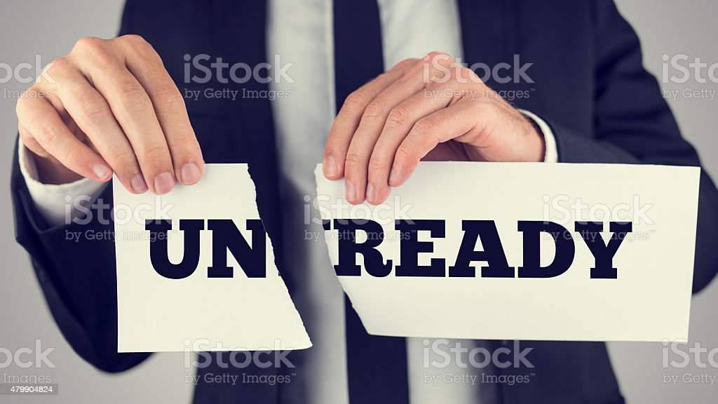 Conceptual Businessman Tearing a White Paper with Unready - Read stock photo