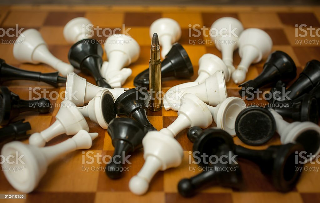 Conceptual photo of weapon power. Bullet among lying chess piece stock photo
