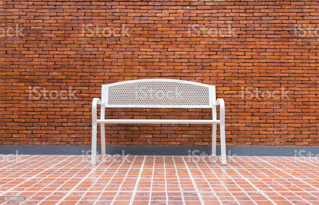 Conceptual white chair empty room with brick wall background. stock photo