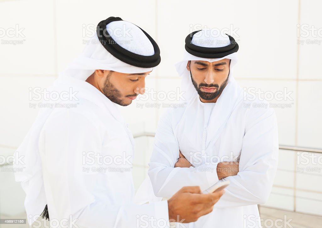 Concerned Arab Businessman Looking at His Colleague's Smartphone Screen stock photo