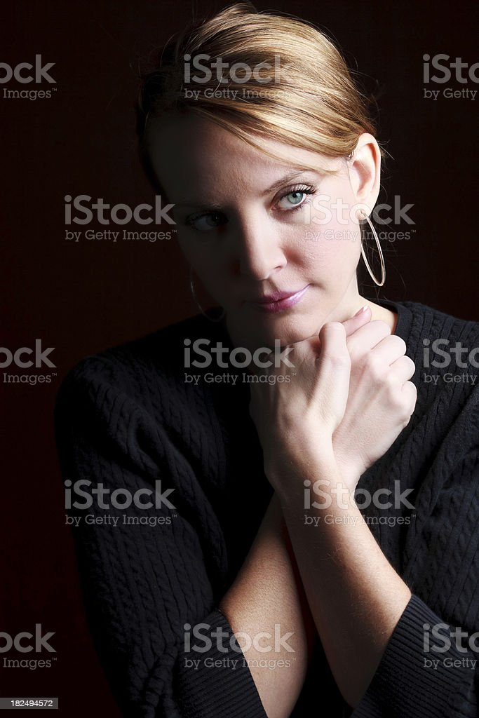 Concerned Beautiful Woman With Hands Together on Black Background royalty-free stock photo