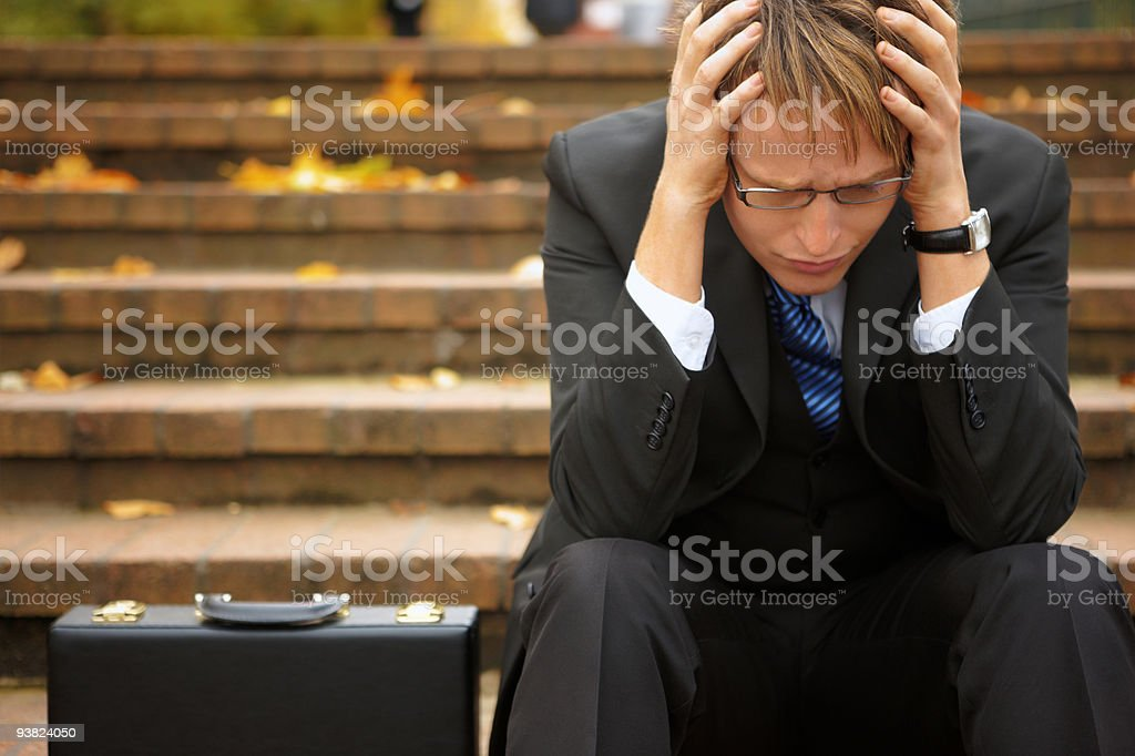 concerned Businessman sitting with head in hands on steps outdoors royalty-free stock photo