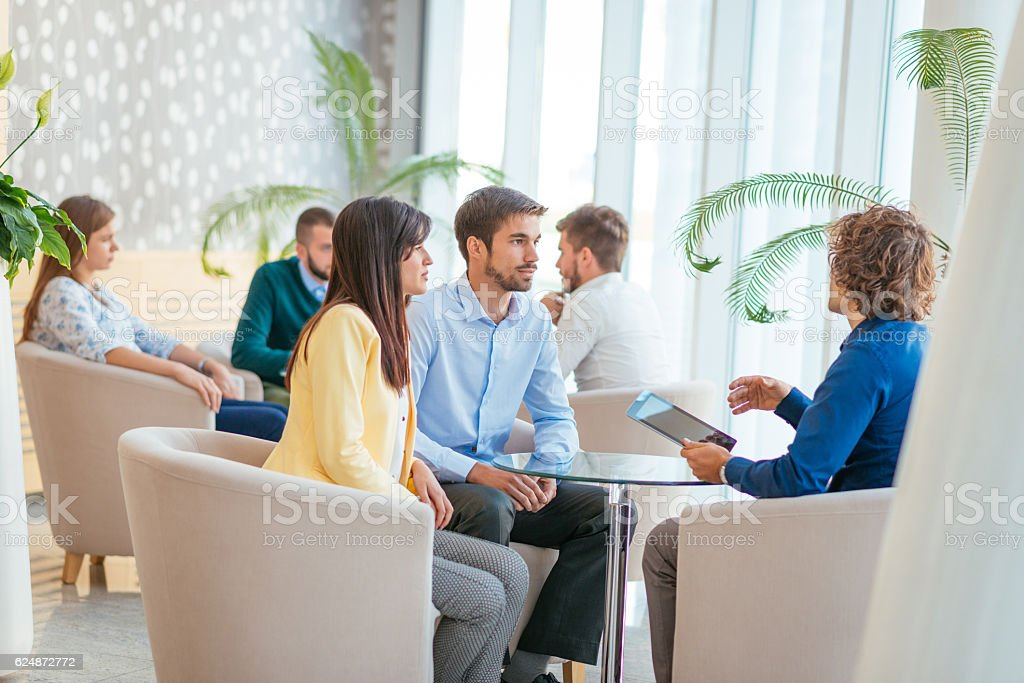 Concerned couple discussing loan rates with personal banker stock photo