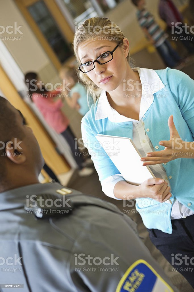 Concerned elementary school teacher taking with police officer in hallway stock photo