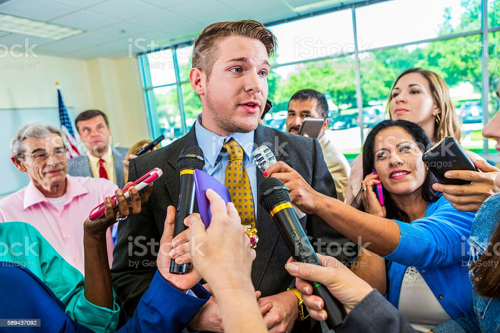 Concerned man answering questions from journalists stock photo