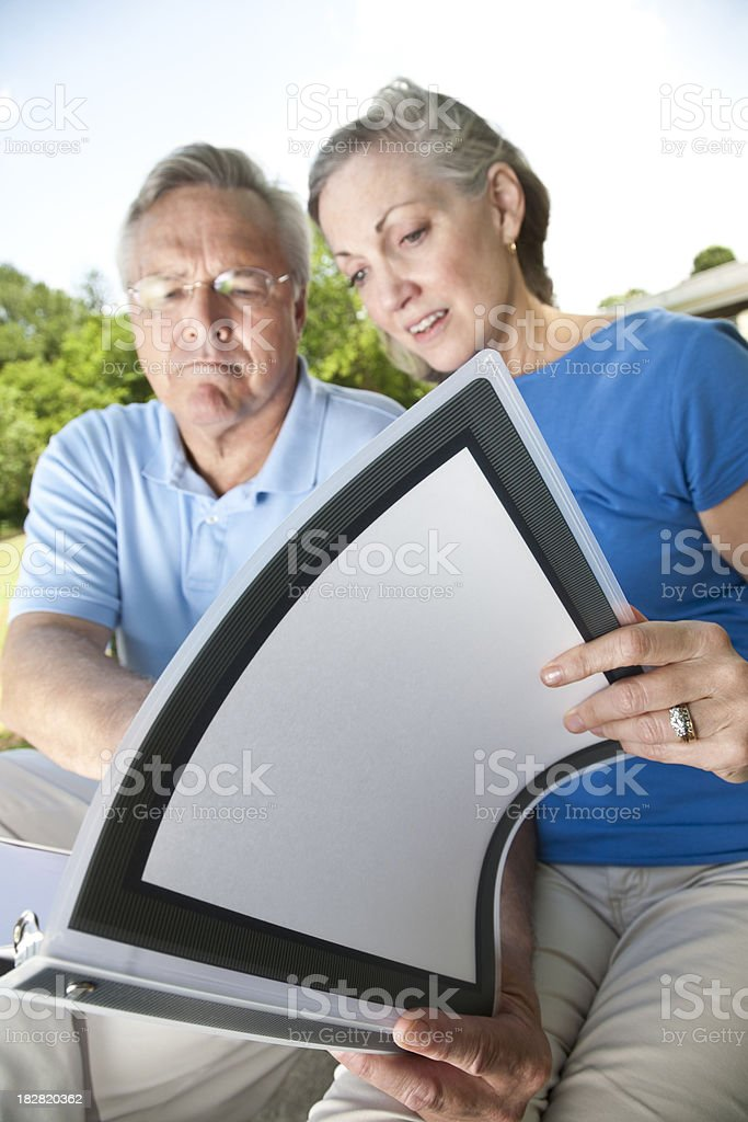 Concerned Mature Couple Looking Over Binder royalty-free stock photo