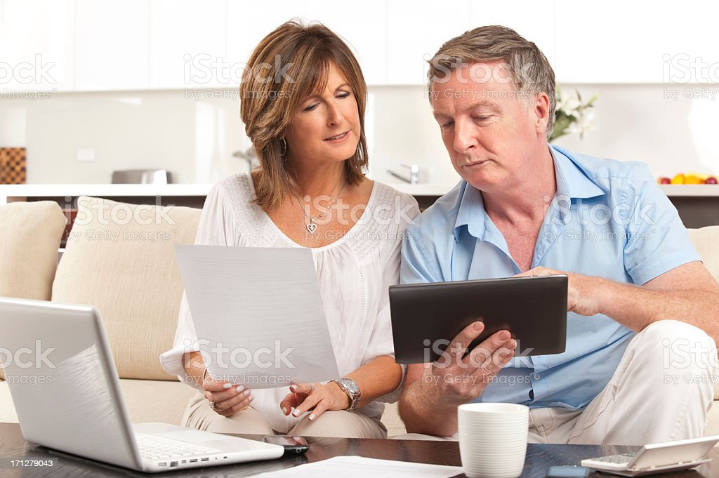 Concerned Mature couple paying bill online using a digital table royalty-free stock photo