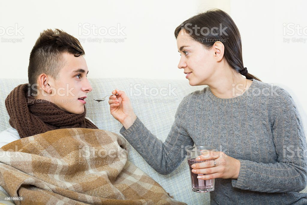 Concerned mother giving mixture to teenage son with cough stock photo